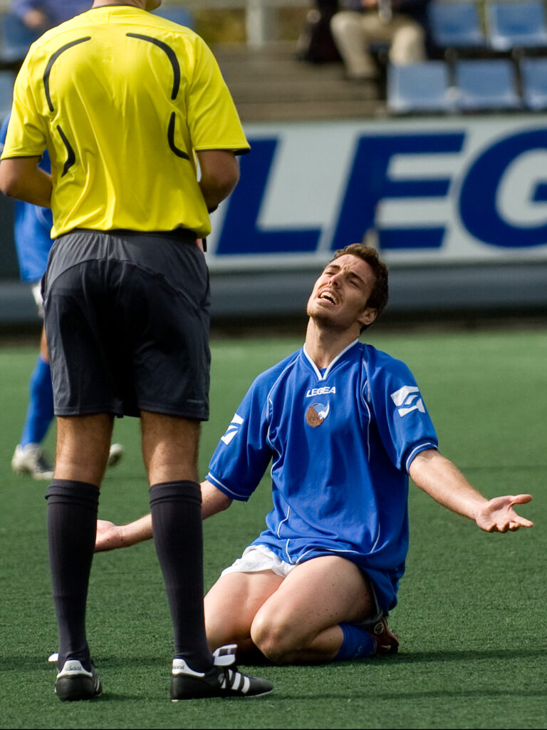 jugador de fútbol recibe una tarjeta amarilla desde el suelo con los brazos cruzados